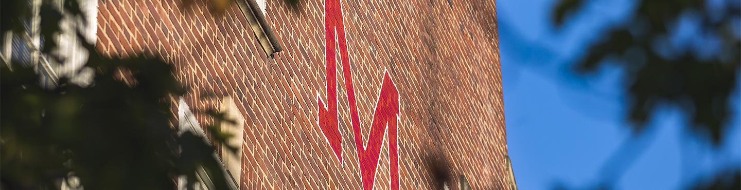 Red M painted on brick building